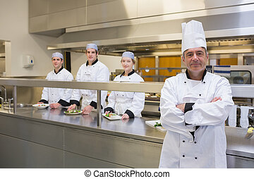 Head chef standing with team behind him - Head chef standing...