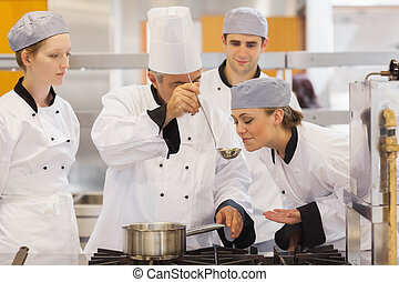 Student tasting the teachers soup in culinary school