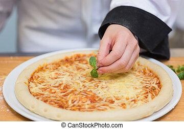 Basil leaf being put on pizza in restaurant kitchen