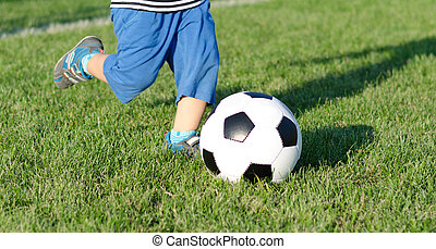 Child kicking a soccer ball - Cropped view of the legs of a...