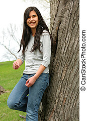 Young teen girl outdoors - Young teen girl leaning against...