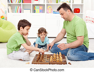 Boys playing chess with their father