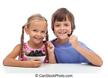 Happy healthy kids eating fresh blackberries