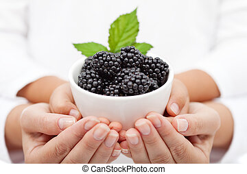 Adult and child hands holding blackberries in a bowl