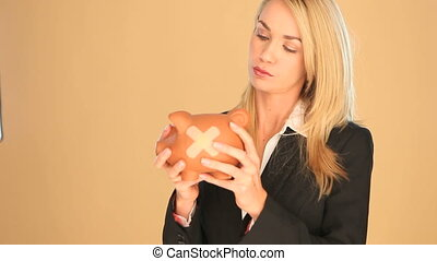Businesswoman with a piggybank - Blonde businesswoman with a...