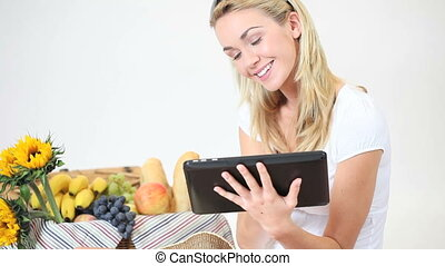 Woman using her tablet at a picnic - Attractive smiling...
