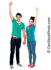 Strong bonding of cheerful teen couple enjoying music. Full...