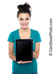 Casual teenager showing newly launched tablet device to the...