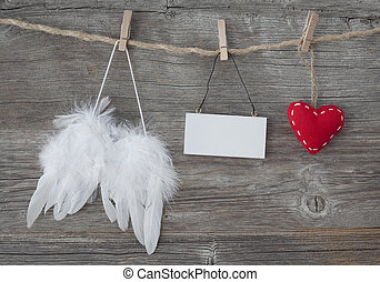 Angel wings with heart and blank note on grey wooden...