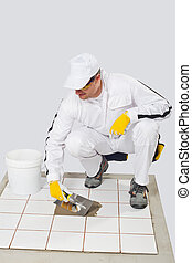 Worker repairs old white tiles with tile adhesive and trowel