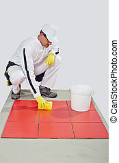worker with yellow gloves and sponge clean red tiles
