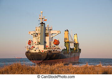 Cargo Ship - Rear view of cargo ship aground near beach