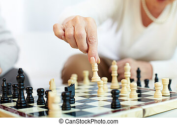 Chess choice - Portrait of senior human hand holding chess...