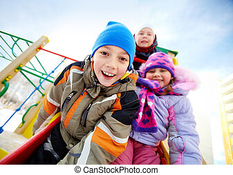 Playful friends - Happy kids in winterwear playing outside...