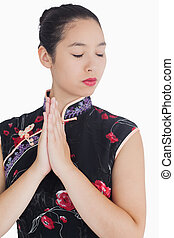 Woman in kimono closing her eyes - Woman with hands together...