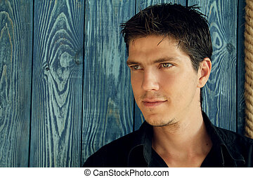 Portrait of young man with very handsome face in black shirt...