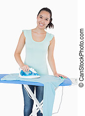 Woman happily doing the ironing on ironing board