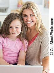 Woman and daughter sitting smiling with laptop