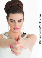 Glamorous woman forming a pistol with her hands and pointing at the camera