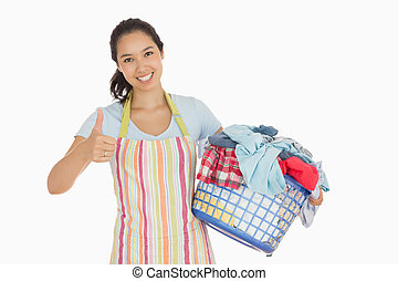 Woman carrying laundry basket and giving thumbs up - Smiling...