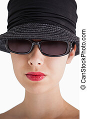 Woman wearing hat and sunglasses with red lips against white...