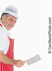 Butcher wielding meat cleaver and smiling - Mature butcher...