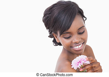 Woman looking at a pink coloured flower while smiling
