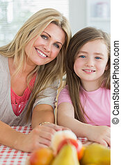Mother and child sitting at kitchen table smiling with fruit...