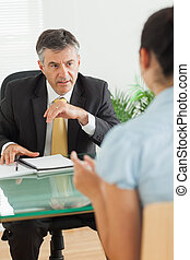 Businessman speaking with a woman in his office