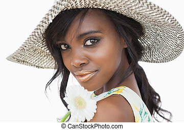 Woman looking while holding daisy and wearing a sun hat