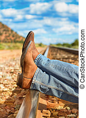across train tracks - famous cow-boy boots and feets across...
