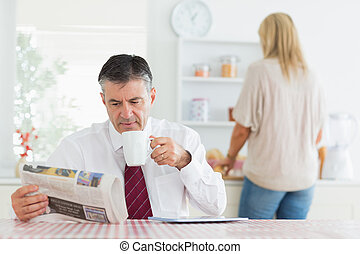 Man sitting at the kitchen table while reading a newspaper...