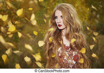 Fashion portrait of a beautiful young woman in autumn forest...