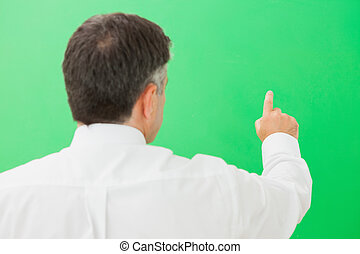 Man pointing on a green screen - Businessman pointing on a...