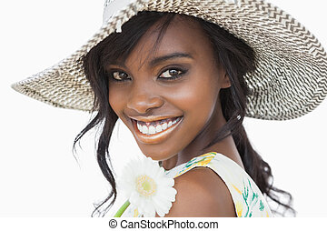 Woman smiling and holding white flower in a sun hat against...