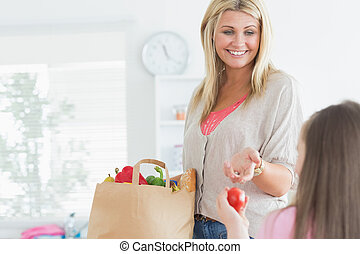Mother passing tomato to child from grocery bag