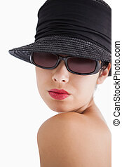 Woman wearing sunglasses and hat looking over her shoulder