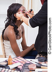 Woman sitting while getting makeup done by make up artisit