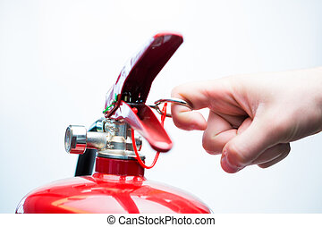 Pulling pin of fire extinguisher - Hand pulling pin of fire...