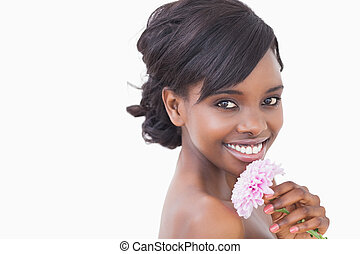 Pretty woman smiling while holding a pink coloured flower...
