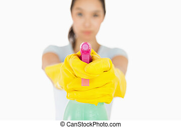 Serious woman pointing a spray bottle at the camera