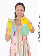 Smiling woman holding out spray bottle