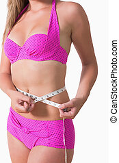 Woman wearing bikini while measuring waist - Woman wearing...