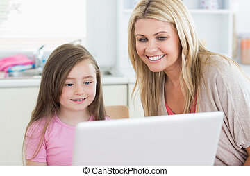 Woman and girl looking at the laptop monitor - Woman and...