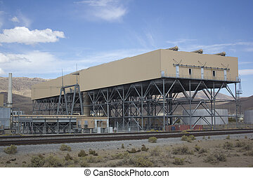 Power plant factory next to train track in the desert
