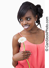 Girl standing holding a white flower while smiling against...