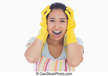 Distressed woman wearing apron and rubber gloves -...