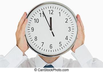 Man hiding face with a clock - Businessman hiding his face...