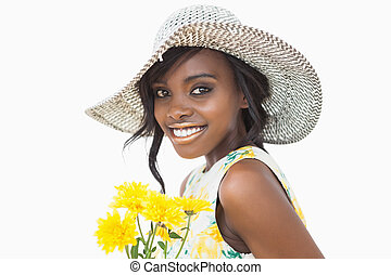 Woman standing while holding yellow flowers against white...