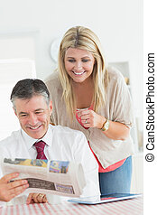 Couple reading a newspaper together - Couple reading a...